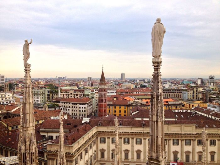 Statues On Milan Cathedral With Cityscape Against Sky