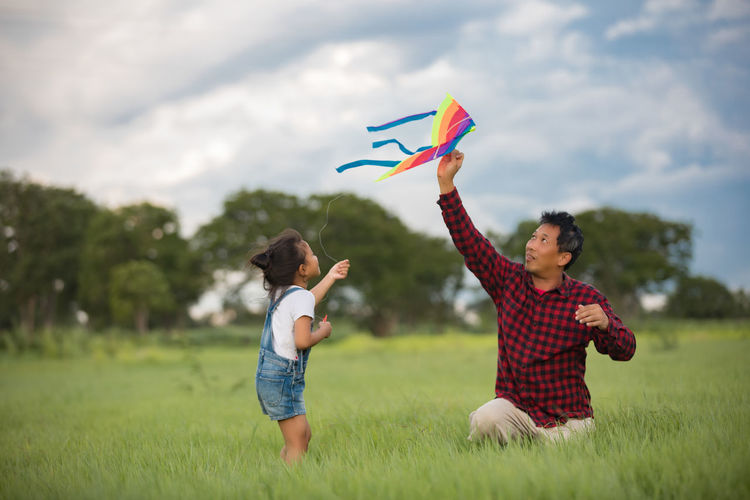 Father and daughter playing with kite on grassy field against cloudy sky