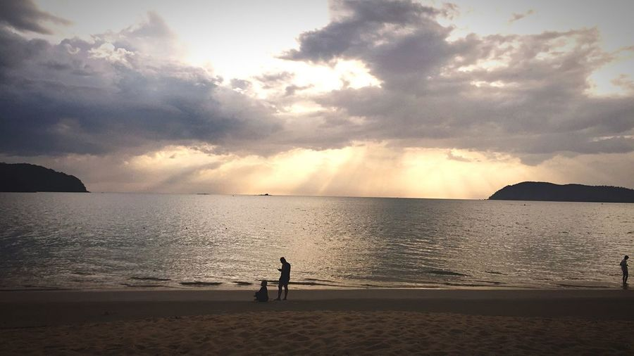 Dramatic Sunburst Over Sea In Background People On Beach