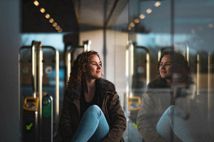 Smiling young woman looking through window