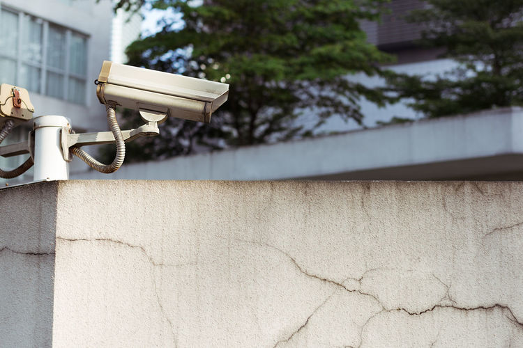 Grey CCTV camera mounted on top of a wall watching over an area. Big Brother Security Spying Architecture Big Brother Watching Building Exterior Built Structure Cctv Close-up Eyes Eyes Watching You Low Angle View Nature Outdoors Security Camera Tree Watching