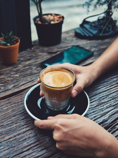 Woman holding coffee cup on table