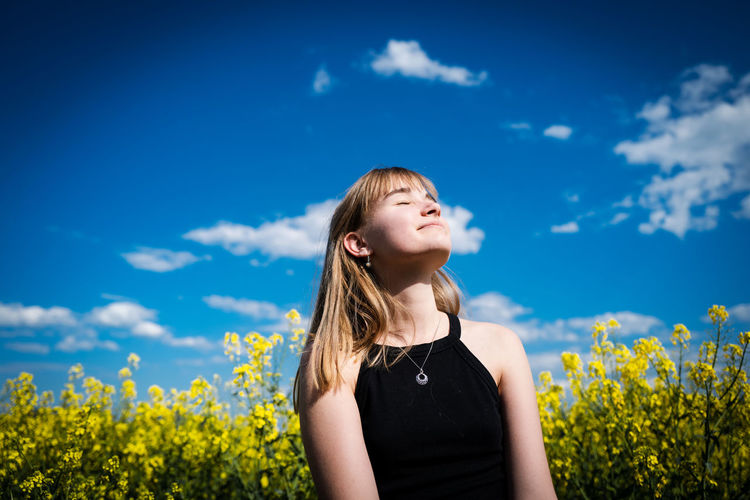 Low angle view of teenage girl with eyes closed sitting against blue sky