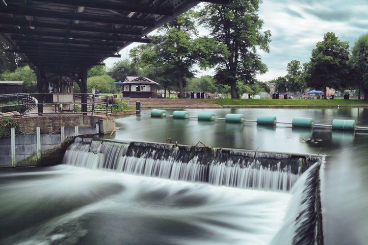 Blurred motion of river below bridge at park
