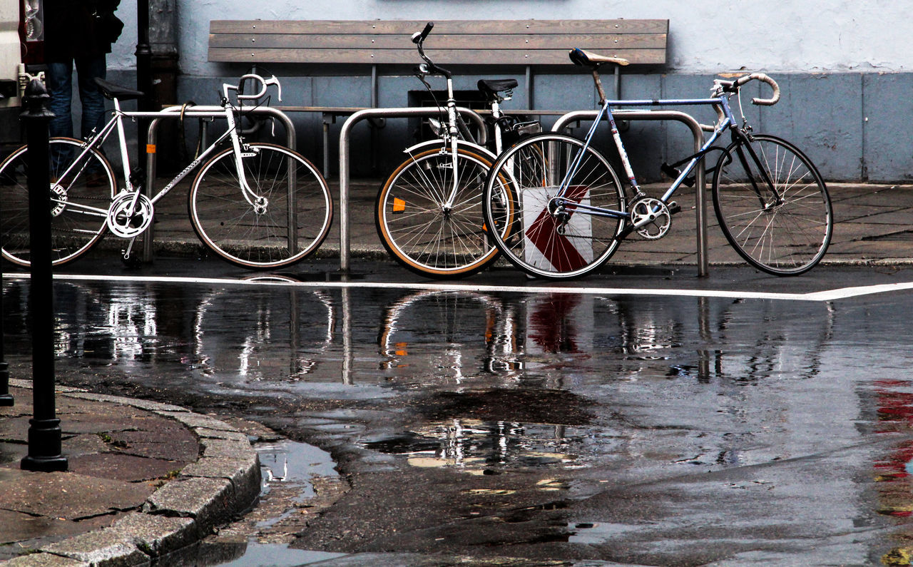 bicycle, mode of transport, transportation, stationary, land vehicle, no people, city, day, outdoors, water, bicycle rack, hanging, architecture