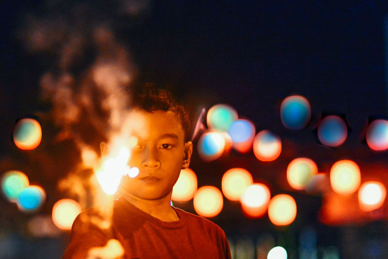 Boy holding lit sparklers in illuminated city at night