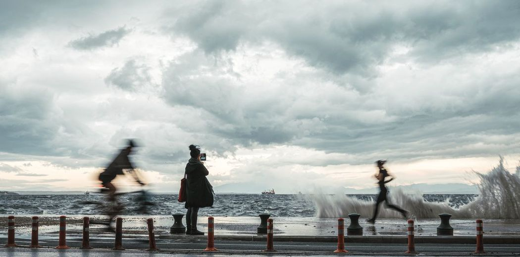 People by sea against sky