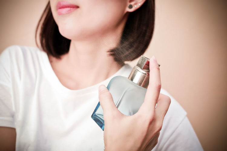 Midsection of woman applying perfume