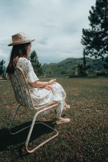 Woman sitting on chair against sky