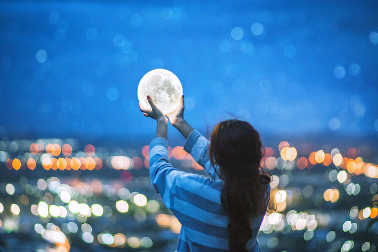 Never stop looking up. 🌕 moon in hand. Celebration Moon Arms Raised Ball Casual Clothing Child Childhood City Focus On Foreground Girls Hairstyle Holding Illuminated Leisure Activity Lifestyles Lighting Equipment Moonlight Night One Person Outdoors Real People Rear View Sky Standing Women