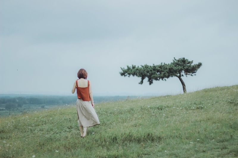Rear view full length of woman standing on grass against sky