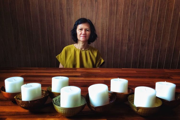 Candles One Person Portrait Front View Women Looking At Camera Wood - Material The Minimalist - 2019 EyeEm Awards Adult Indoors  Waist Up Real People Females Lifestyles Smiling Casual Clothing Table Clothing