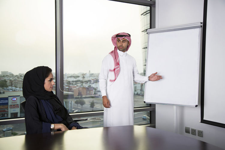 Man Standing By Whiteboard Looking At Woman In Office