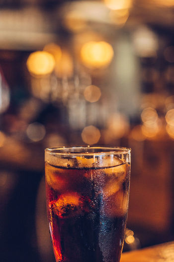 Close-up of cold coke glass at a bar counter