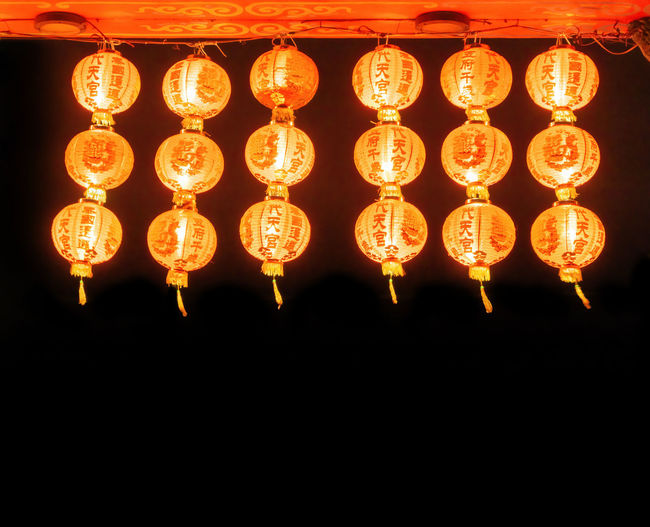 Low angle view of illuminated lanterns hanging in the dark
