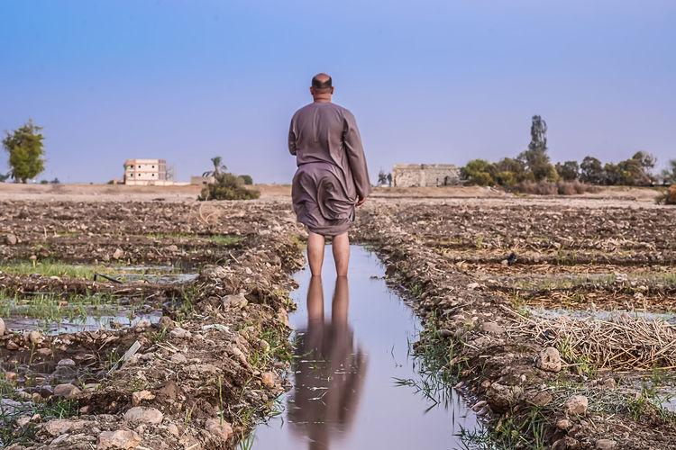 Man Walking In Field Against Clear Sky
