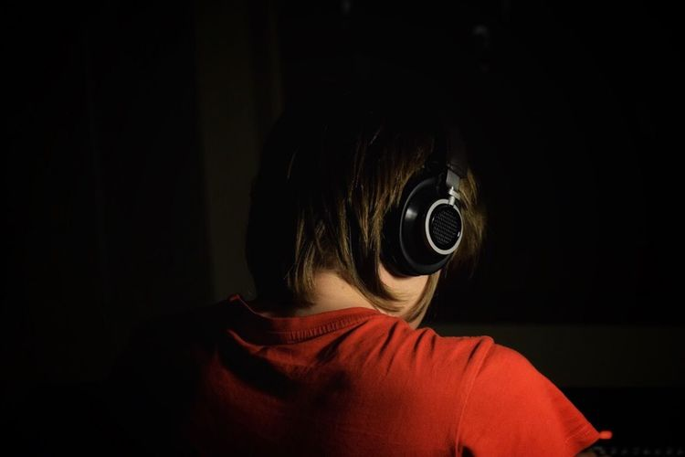 Rear View Of Teenage Boy Listening To Music Against Black Background
