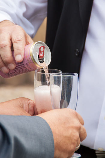 Midsection Of Man Pouring Drink For Male Friend