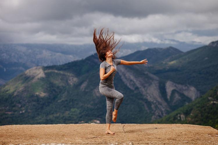 Full length of woman exercising on cliff against sky