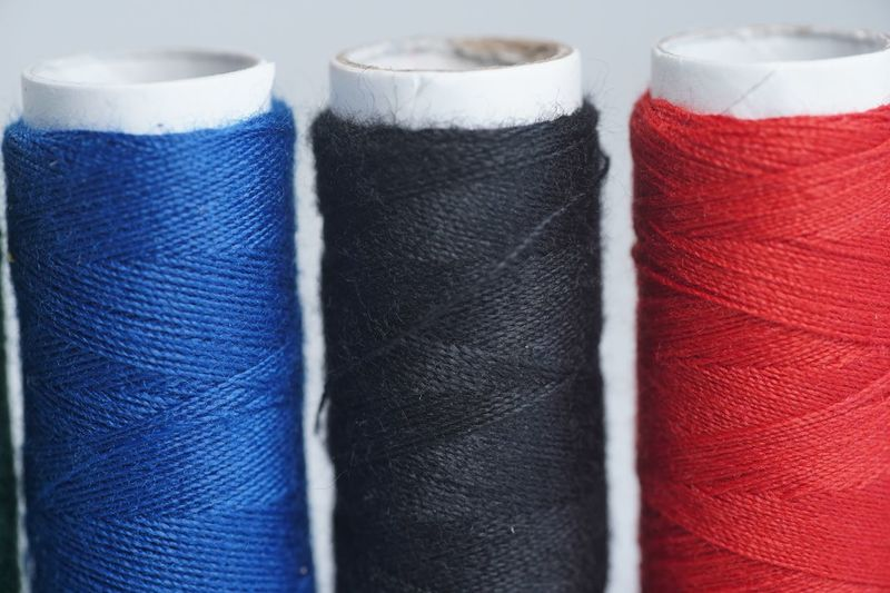 Close-up of multi colored thread spools on white background