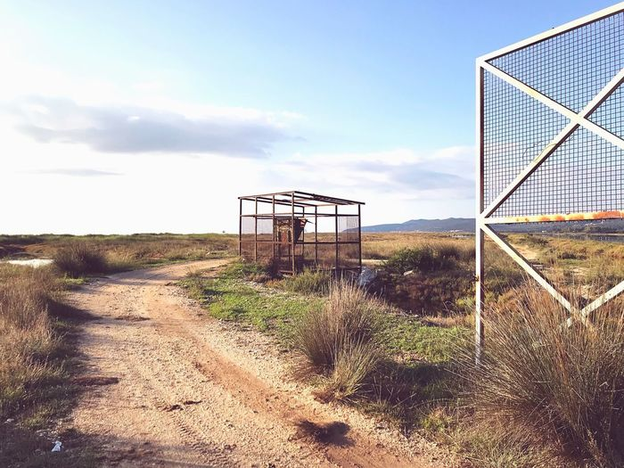 Environmentalist Abandoned Metal Structure Fence Sky Land Nature Day Cloud - Sky Built Structure Architecture No People Sunlight Outdoors Tranquil Scene Tranquility Water Grass Sand