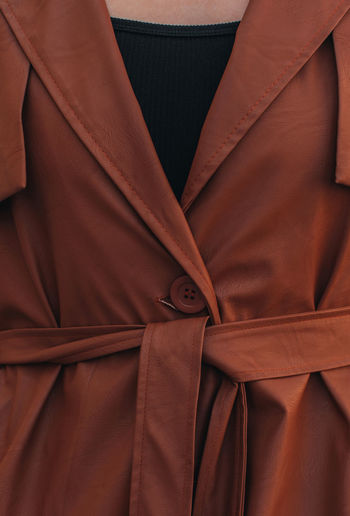 Street style fashion details of autumn trench, leather long stylish brown coat. female outfit.