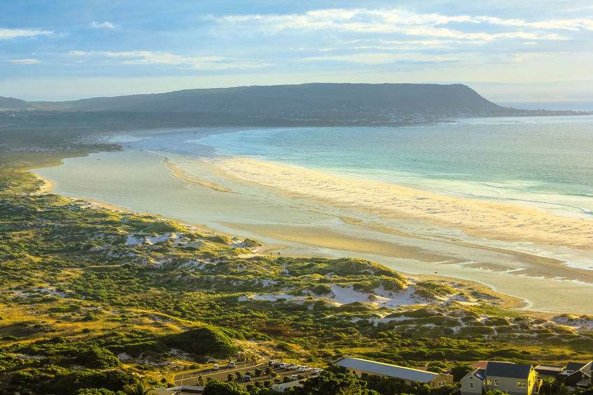 Panorama of Noordhoek Beach, 8 km of sandy beach from Chapmans Peak Drive to Kommetjie, in Table Mountain National Park, South Africa at sunset. Noordhoek beach is popular for horse riding and surfing. Big waves in a sunny day with blue sky. Extreme sports leisure concept. Powerful waves background with copy space. Summer vacation concept. Calm sea at sunset with golden background Noordoek Beach in the spectacular Table Mountain National Park, Cape Town, South Africa. Peace, relaxation, summer, holidays concept. Copy space. Cape Town Noordhoek South Africa Surf Table Mountain Aerial View Africa Beach Beauty In Nature Cloud - Sky Day Horizon Over Water Landscape Mountain Nature No People Noordhoek Beach Outdoors Scenics Sea Sea And Sky Seascape Sky Sunset Town Tranquil Scene Tranquility Tree Water Waves Crashing