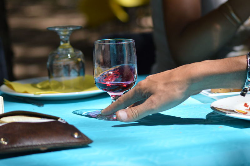 Midsection of man holding wine glass on table at restaurant