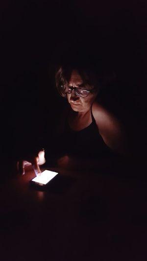 Mature woman using mobile phone in darkroom