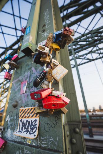 Low angle view of padlocks hanging on metal bridge