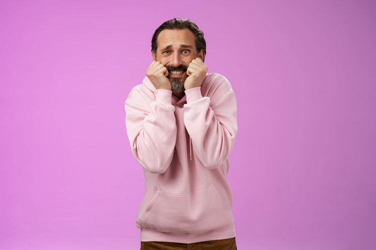 Portrait of young man standing against pink background