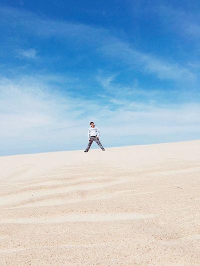 Man standing on sand at desert against sky