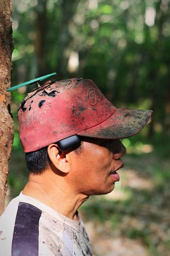 Side view of man wearing messy cap by tree