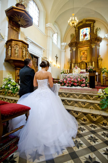 Altar Couple In Church Bouquet Bride Bride And Groom Bridegroom Celebration Celebration Event Ceremony Flower Full Length Kneeling Girl Life Events Lifestyles Love Married Rear View Religion Togetherness Wedding Wedding Ceremony Wedding Dress Wedding Dresses Wife