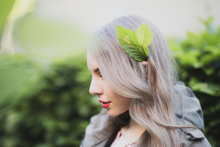 Close-up of young woman with leaves in hair