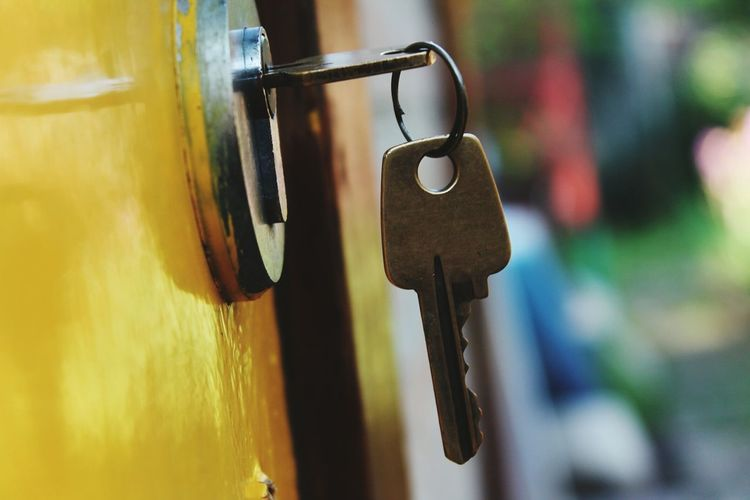 Close-up of keys in hole on yellow door