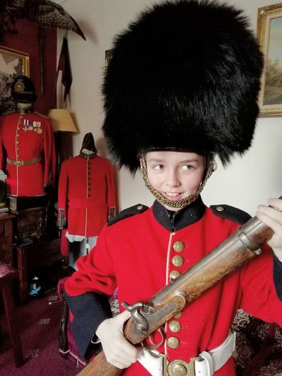 time traveling Young Boy Boy Bearskin Small Soldier Georgian Military Uniform Military Period Costume Queens Guard When I Grow Up... Red Tunic Uniform Brass Buttons Musical Instrument Musician Playing Looking At Camera Period Costume Historic