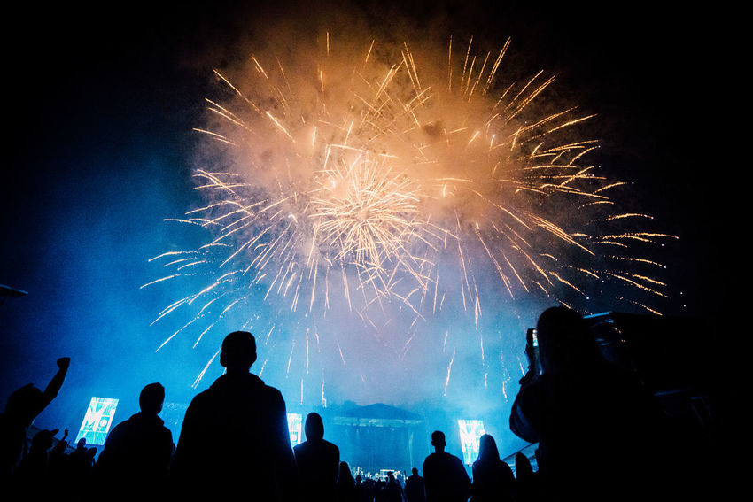 Adult Arts Culture And Entertainment Celebration Crowd Enjoyment Event Excitement Exploding Firework Firework - Man Made Object Firework Display Illuminated Large Group Of People Leisure Activity Lifestyles Low Angle View Men Night Outdoors People Real People Silhouette Sky Women