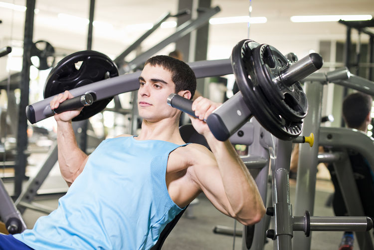 Young man exercising on equipment in gym