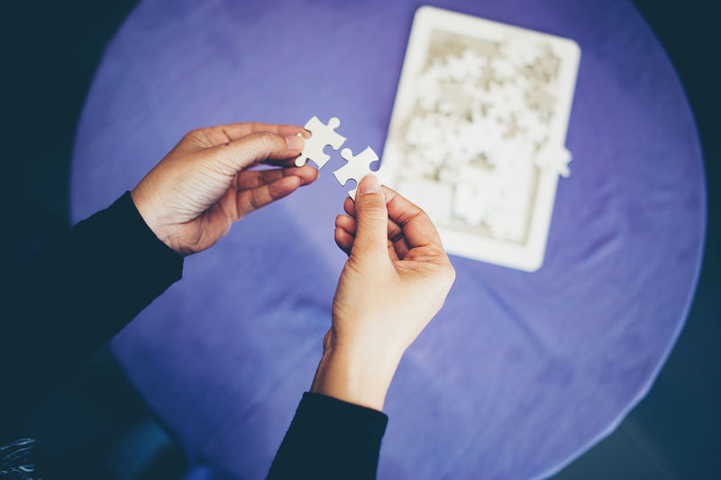 Cropped Hands Of Woman Holding Jigsaw Puzzles Over Table