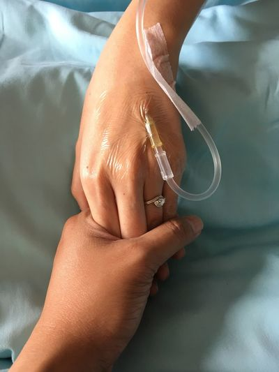 Cropped Image Of Woman Holding Patient Hand With Iv Drip In Hospital