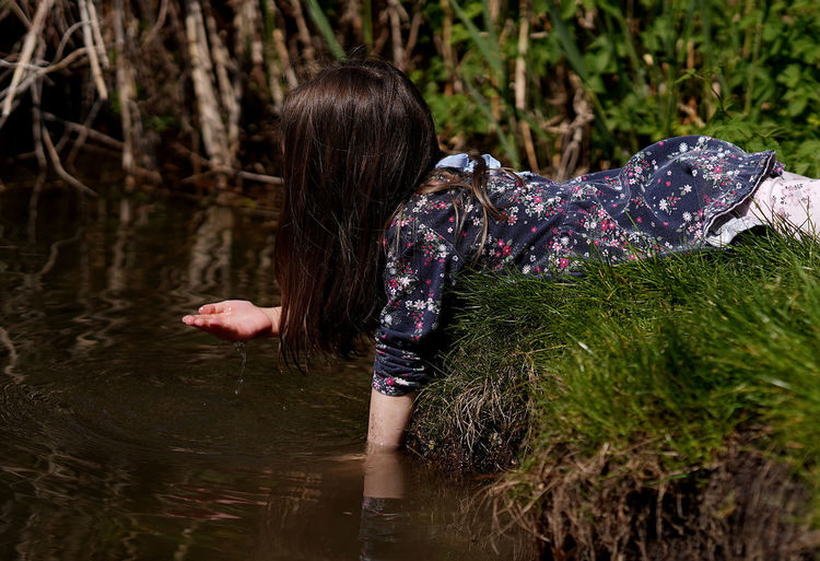 Rear view of woman by plants against lake