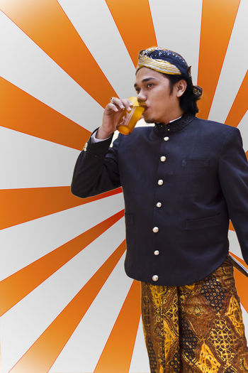 Young man wearing traditional clothing while drinking fresh jamu against pattern wall