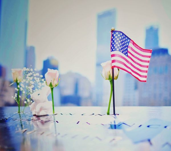 American Flag By Roses On Table
