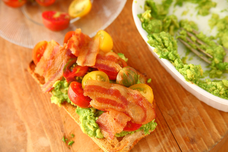 Tomatoes and bacon on avocado toast Food Freshness Cutting Board Wood - Material Ready-to-eat No People Meal Snack Bacon Cherry Tomatoes Avocado Toast  Mashed Avocado Breakfast Pork Overhead Natural Light Studio Shot Textures Delicious Dishes Closeup Indoors  Home Cooking Cured Meat