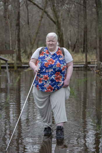 Full length of woman walking in lake against trees at forest