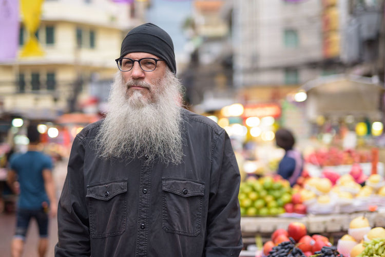 Portrait of man standing at market in city