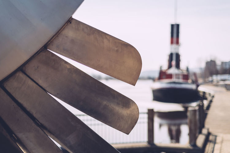 Close-Up Of Propeller Against Boat Moored On Lake