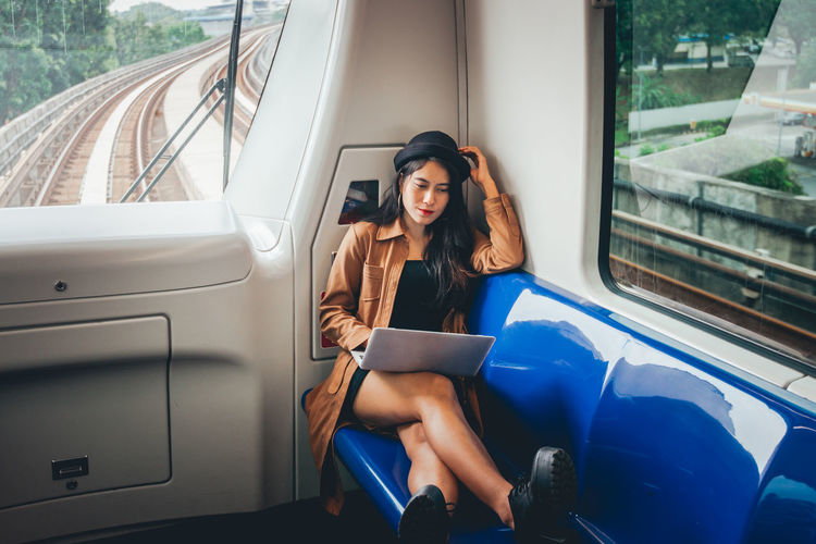 Full length of woman using laptop while sitting in train