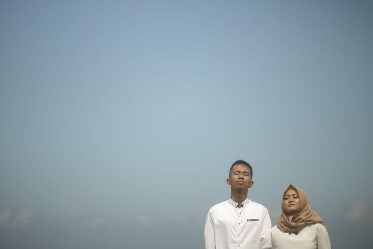 Portrait of a couple standing against clear sky